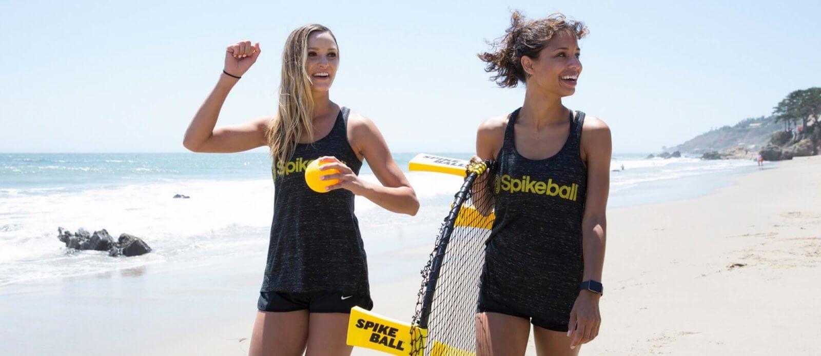Zwei Frauen mit einem Spikeball Set am Strand